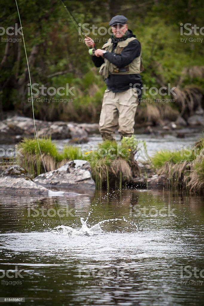 Fly fisherman grey cap vest blurry stock photo