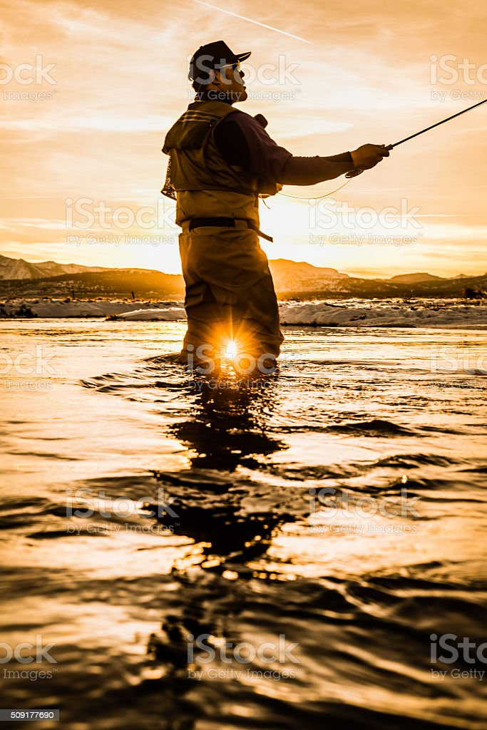 Fly Fisherman High Sticking In The River At Sunset stock photo