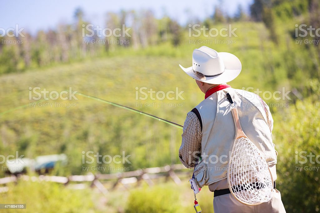Fly fisherman holding fishing rod while standing in river royalty-free stock photo