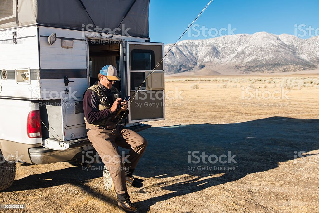 Fly Fisherman On His Cell Phone stock photo