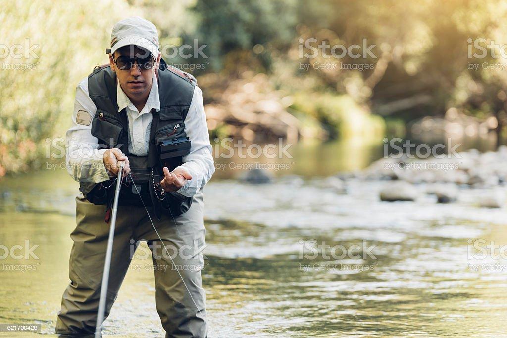 Fly fisherman using flyfishing rod. stock photo