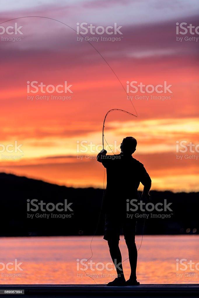 Fly Fishing Fisherman Silhouette on Lake at Sunset stock photo