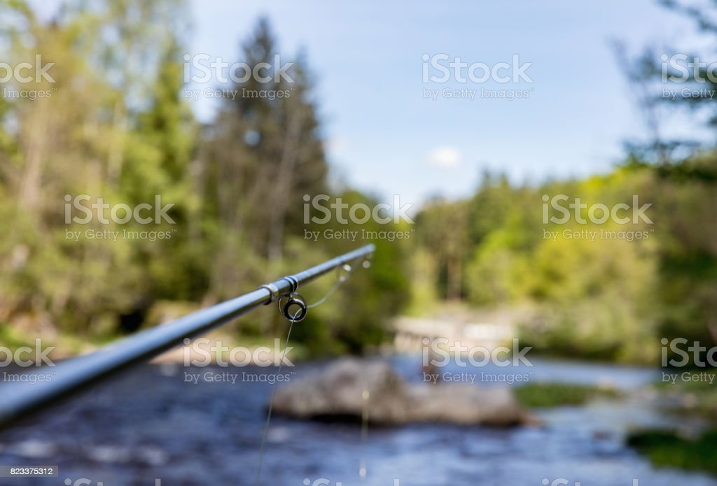 Fly fishing. Rod with fly fishing reel. In the background the river. stock photo