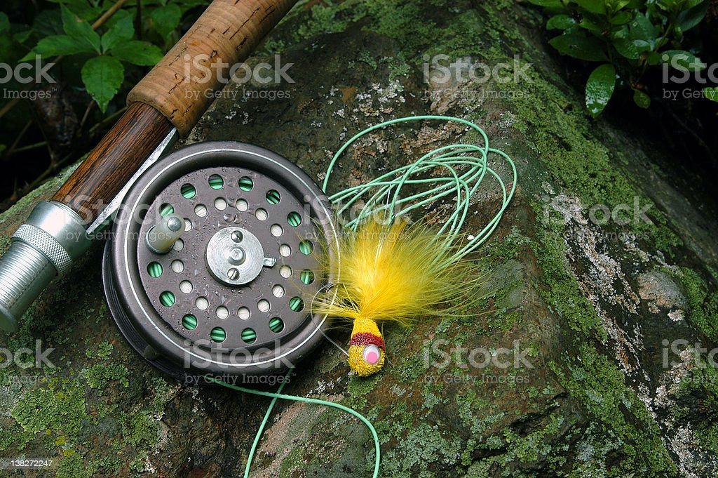 A fly fishing tackle on the rocks royalty-free stock photo