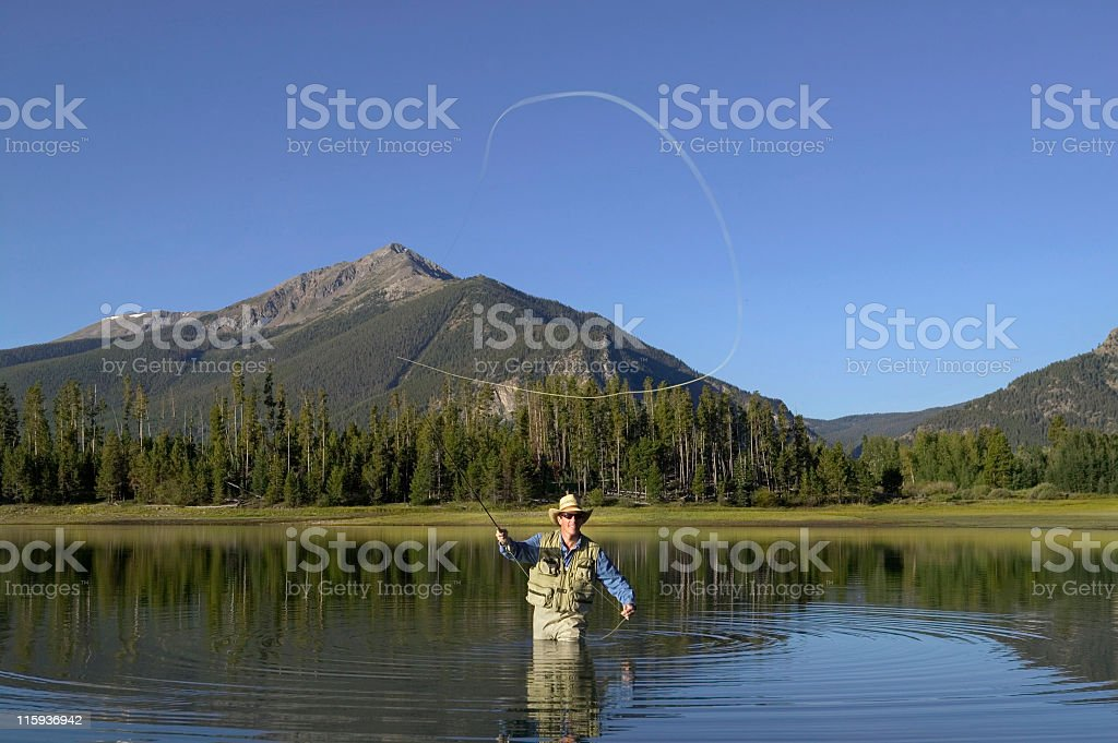 Fly Fishing with Waders  in Mountain Lake royalty-free stock photo