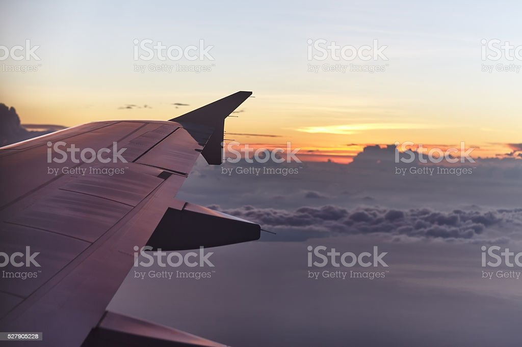 flying aircraft wing on beautiful sunset stock photo