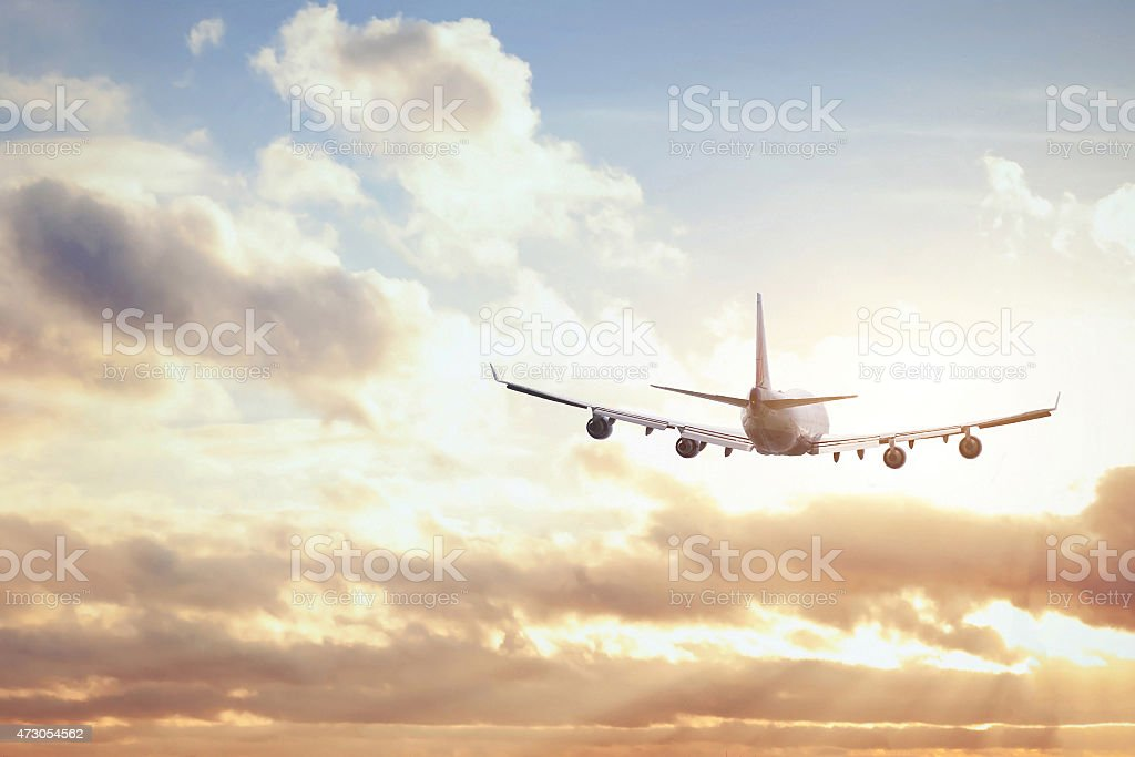 Flying airplane in the sky below clouds on a sunny day stock photo