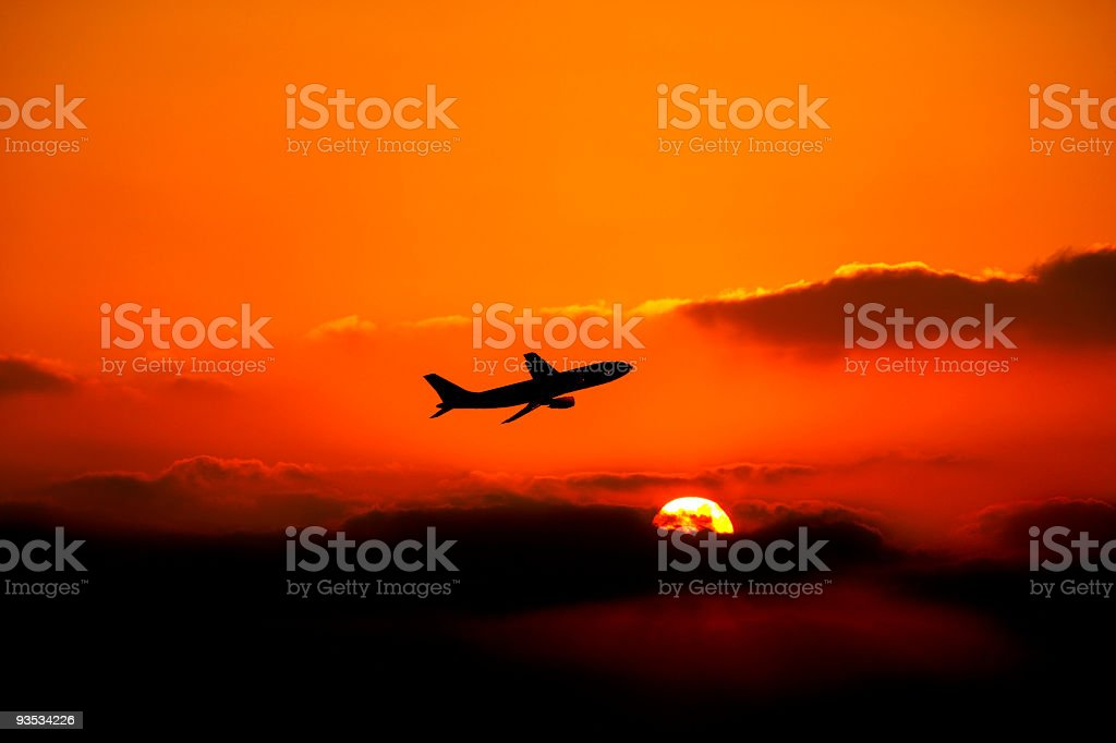 flying airplane over sunset stock photo