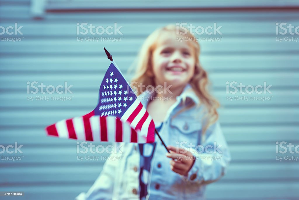 Flying american flag in girl'€™s hand. Selective focus on flag stock photo
