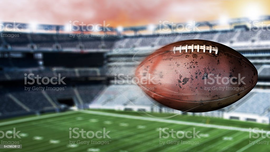 Flying american football leaving a trail of dust and smoke. stock photo