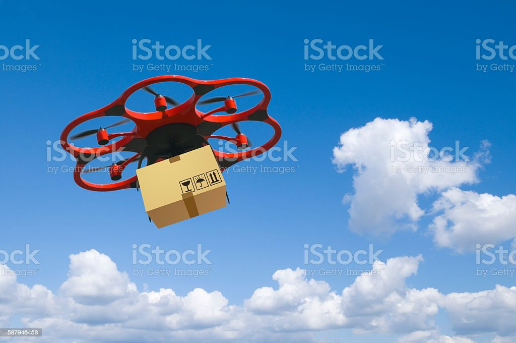 Flying arial drone with a packet and cloudy sky stock photo