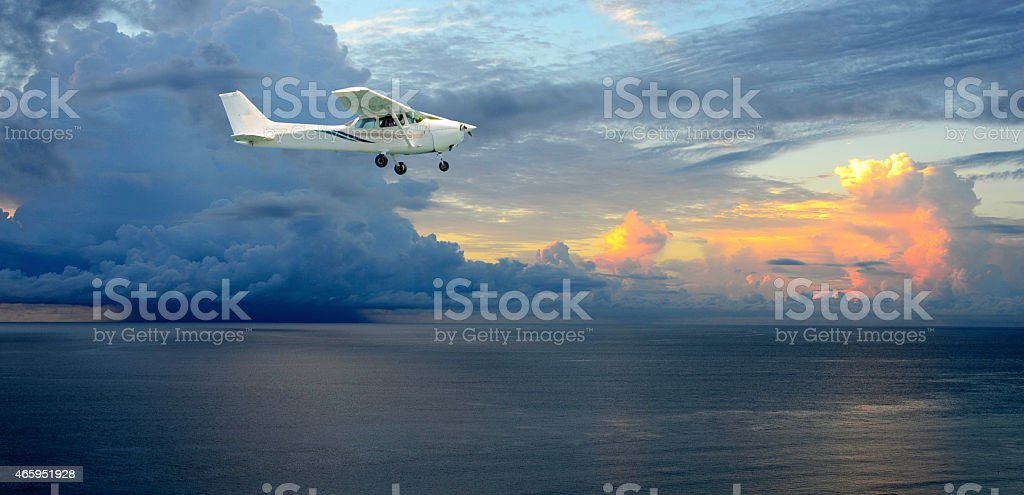 A plane flying by a thunderstorm. The plane is flying over the clear...