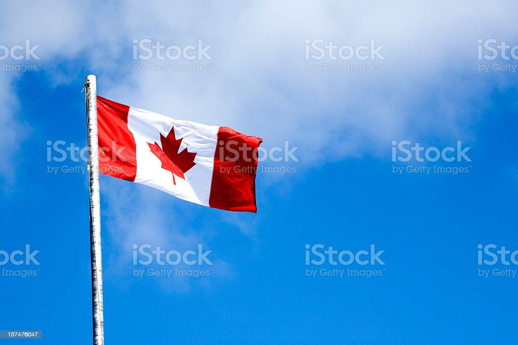 A flying Canadian flag on a sky blue background royalty-free stock photo