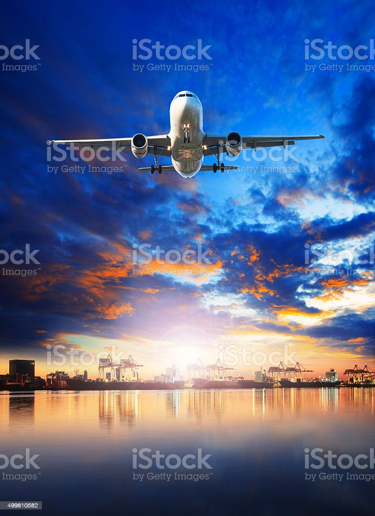 flying cargo plane over shipping port behind stock photo