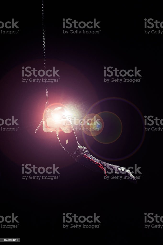 Flying circus artist in bright spotlight stock photo