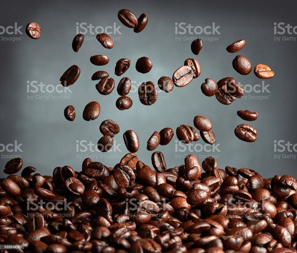 Flying coffee beans over dark background stock photo