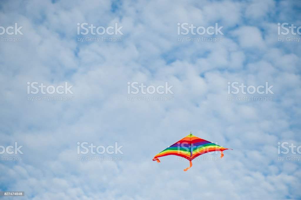 flying colorful kite on cloudy blue sky background stock photo