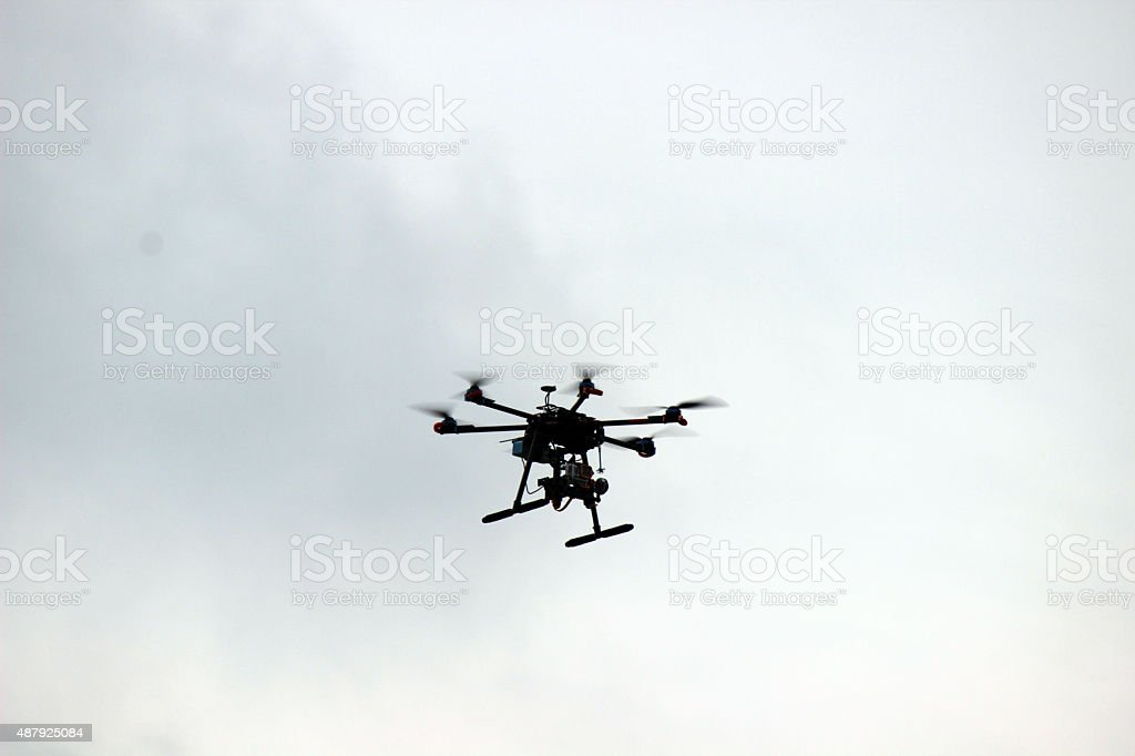 Flying Dark-colored Drone in Cloudy Sky stock photo