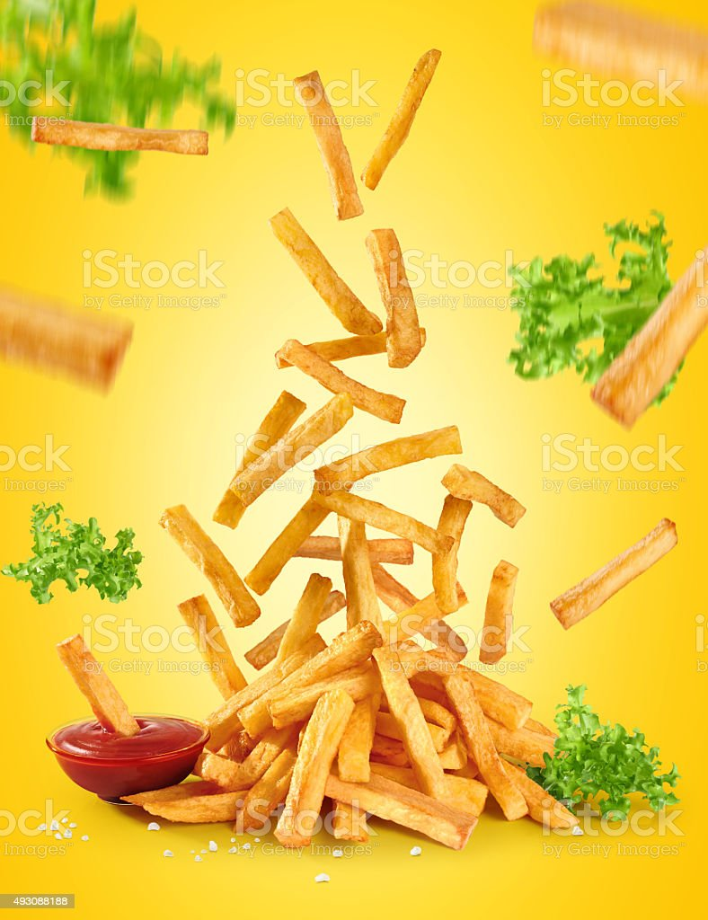 Flying fried potatoes, lettuce and ketchup. French fries. stock photo