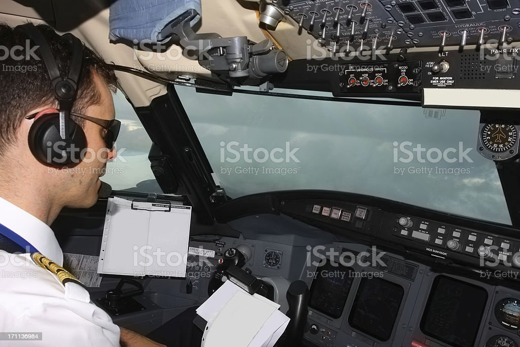 Flying in bad weather...Young pilot at work,checkig data royalty-free stock photo