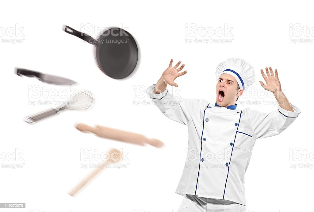 Flying kitchen utensils towards stunned chef royalty-free stock photo