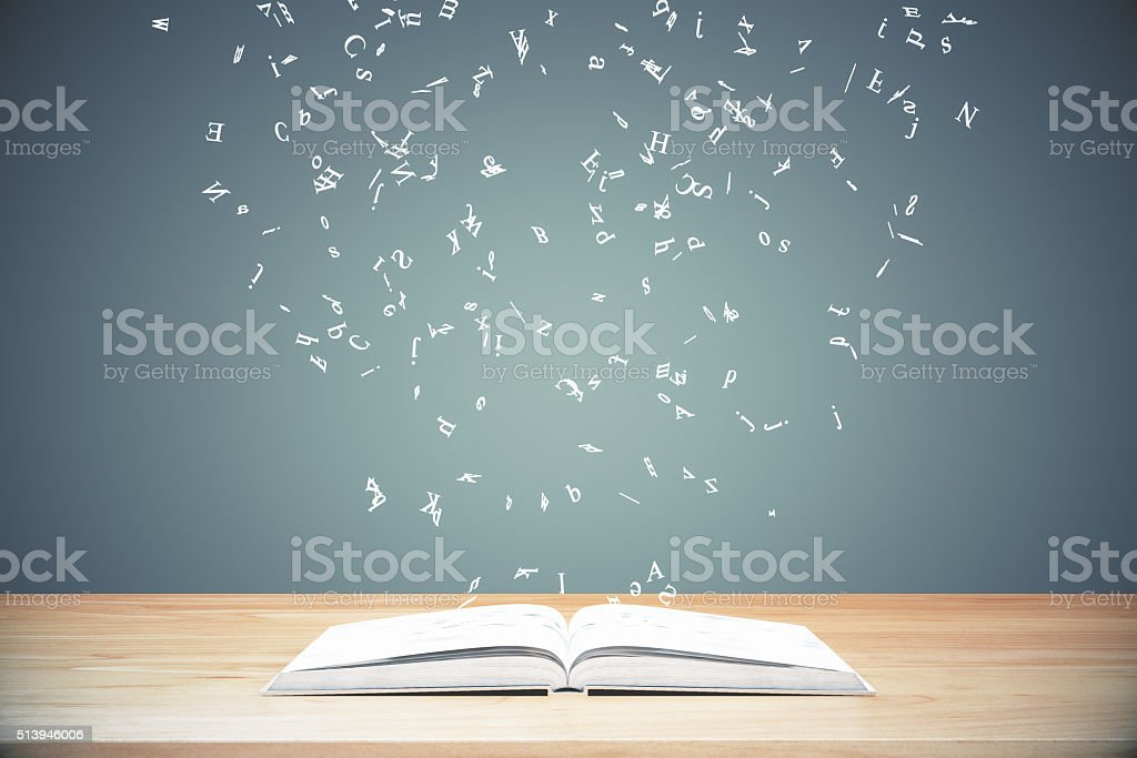 Flying letters from the opened book on wooden table stock photo