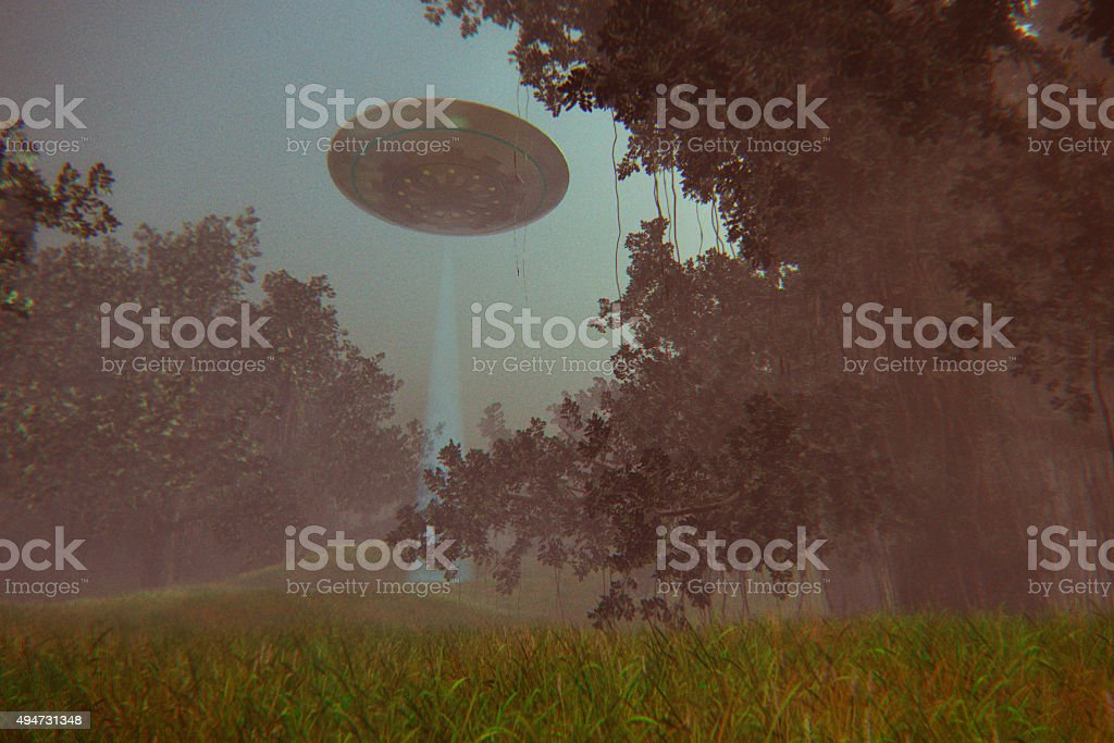 UFO flying over forest at night stock photo