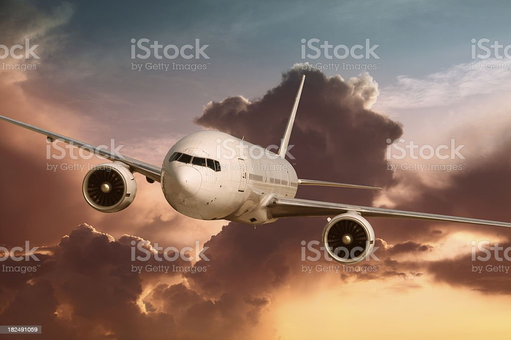 Flying Passenger Airplane in Sunset Light royalty-free stock photo