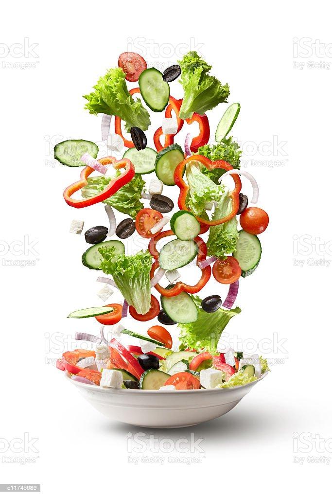flying salad isolated on white background stock photo