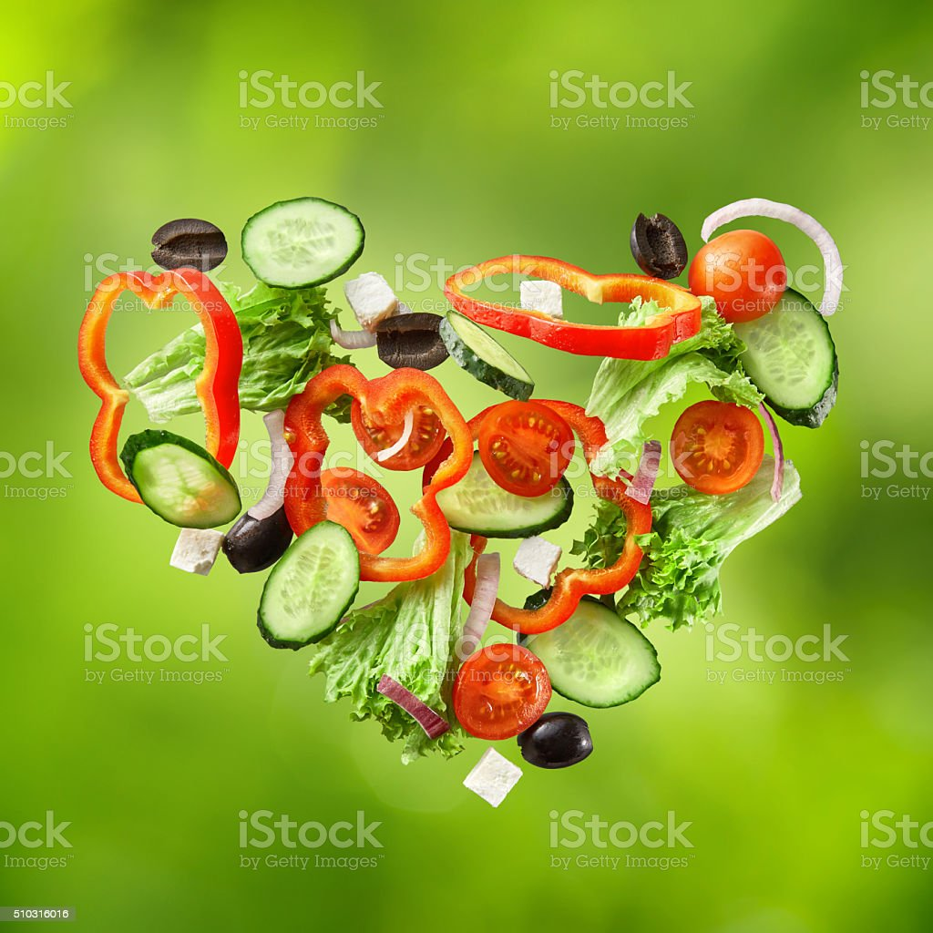 flying salad on natural green background stock photo