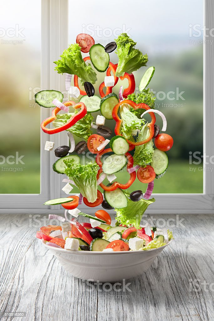flying salad on wood against window stock photo