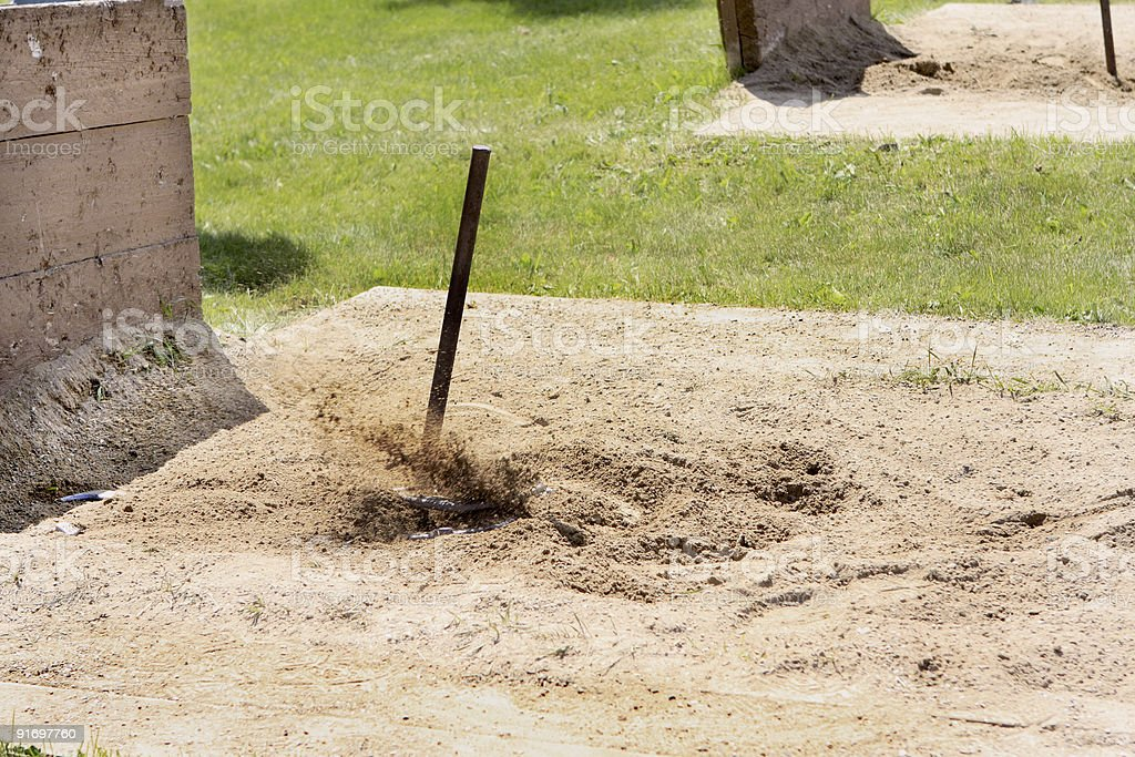 Flying sand as the Horseshoe ringer is made. stock photo