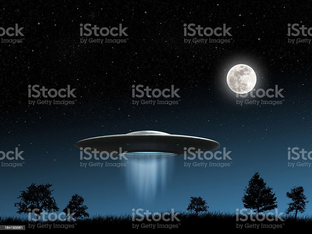 Flying saucer over field with full moon stock photo