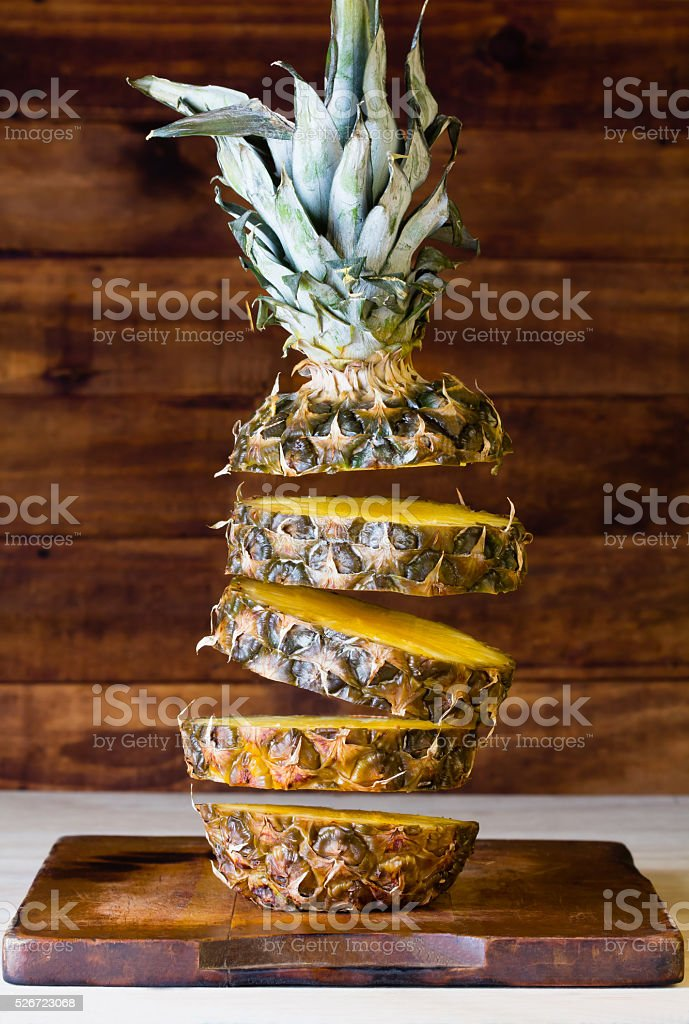 Flying slices of pineapple on wooden background stock photo