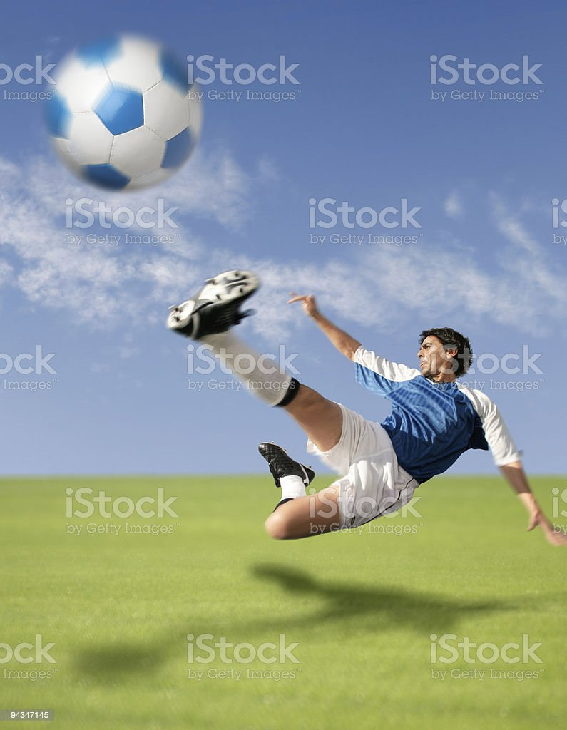 Flying soccer player hitting the ball stock photo
