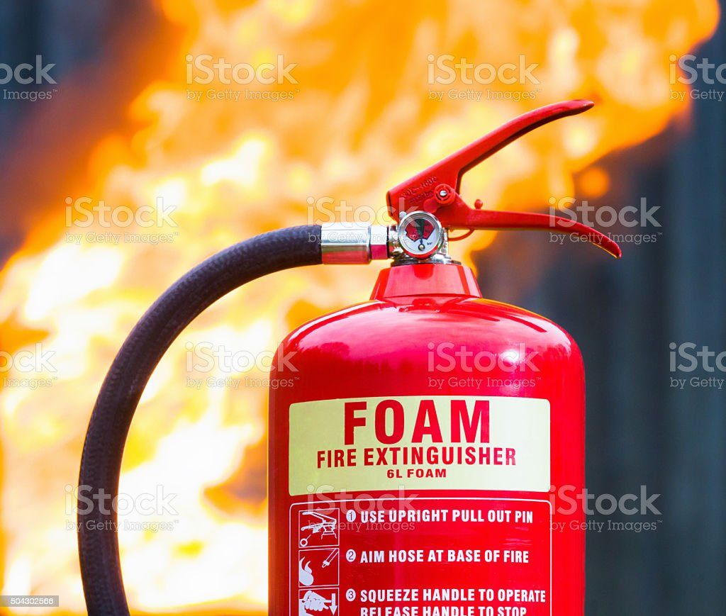 Foam fire extinguisher closeup with fire behind stock photo