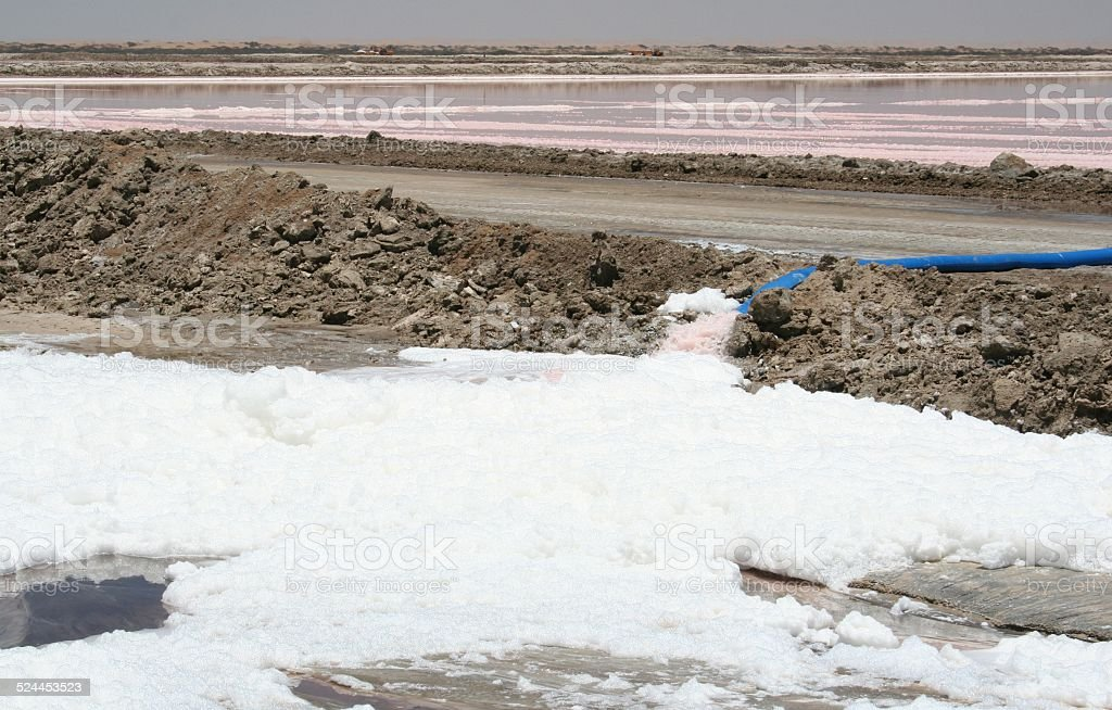 Foam in Salt evaporation ponds with red Microorganisms, Swakopmund, Namibia stock photo