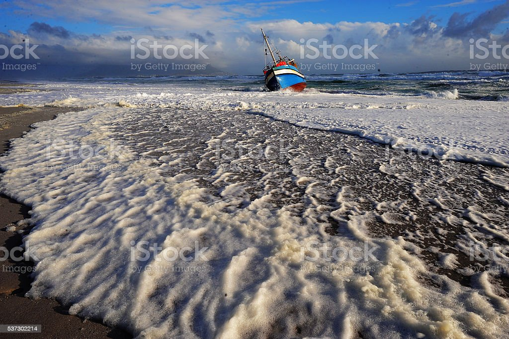Foamy sea water washes up with beached ship stock photo
