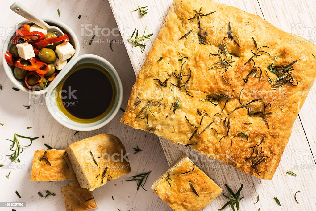 Focaccia bread with rosemary herb and olive accompaniments stock photo