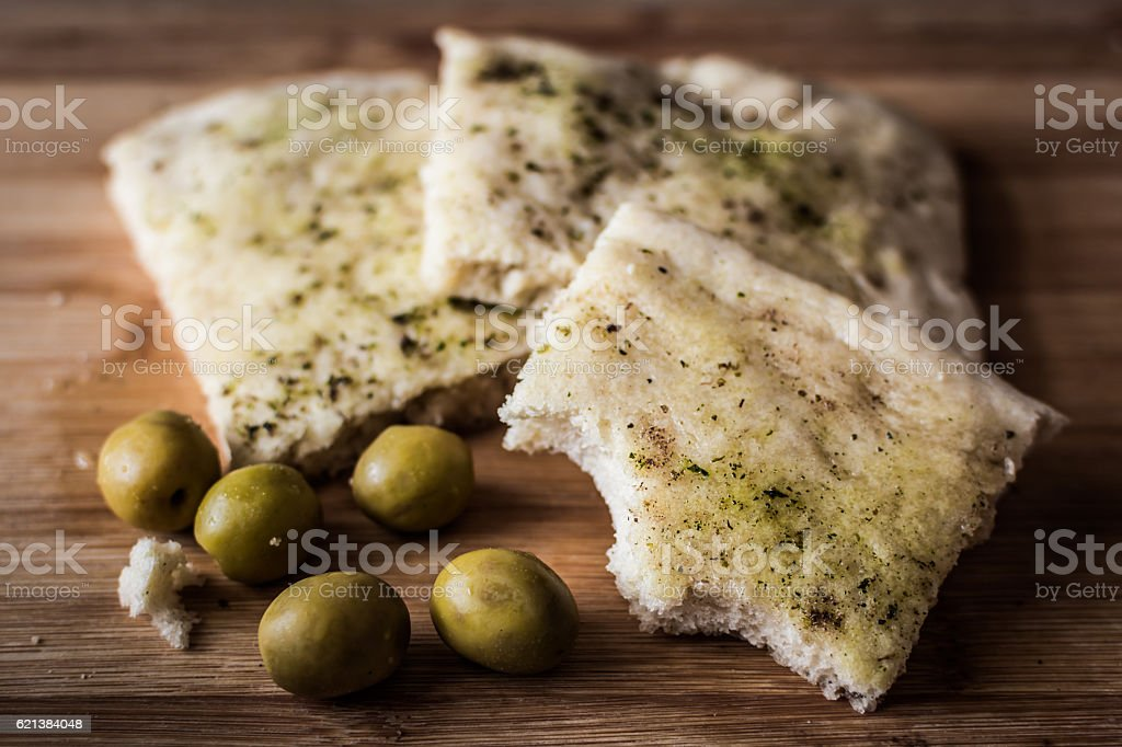 Foccaccia and olives on a table. stock photo