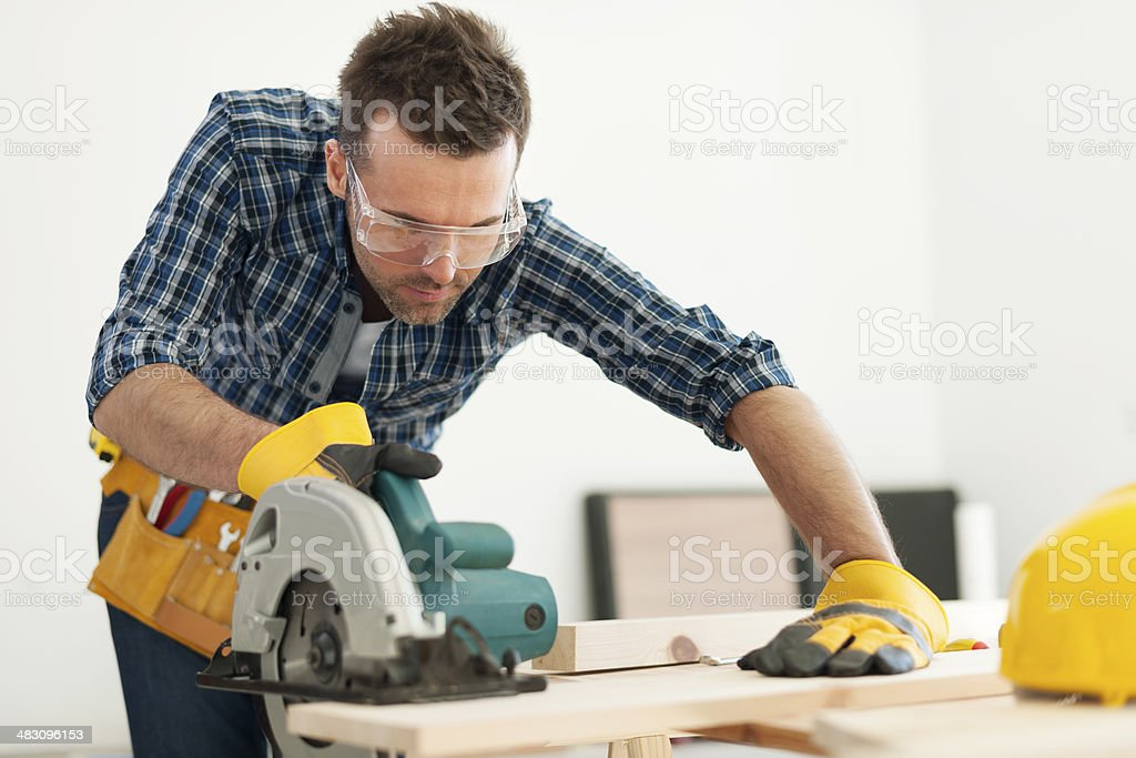 Focus carpenter sawing wood board stock photo