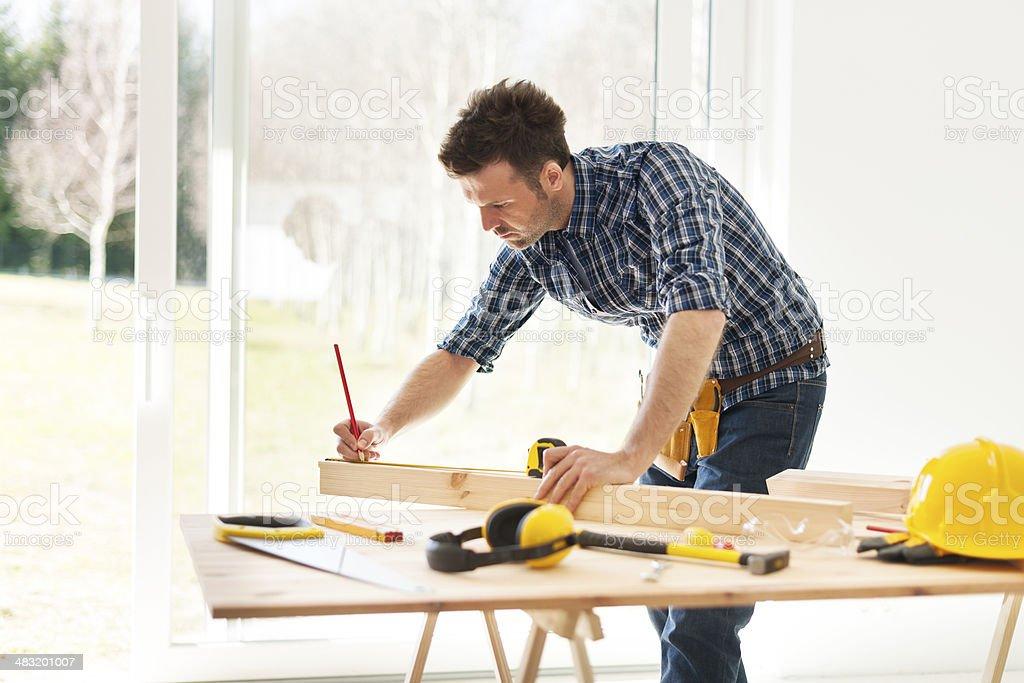 Focus man measuring wooden planks stock photo