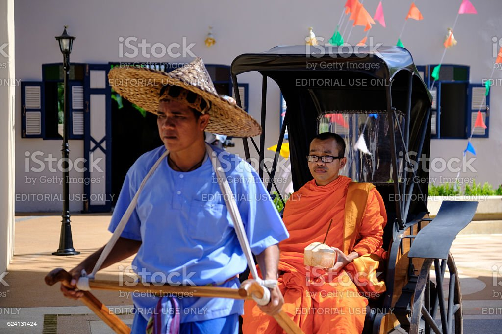 Focus monk on Old rickshaw in thailand ancient simulation park. stock photo