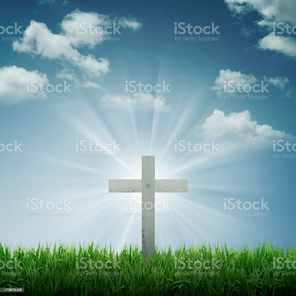 Focus on a white cross with sun rays and blue sky stock photo