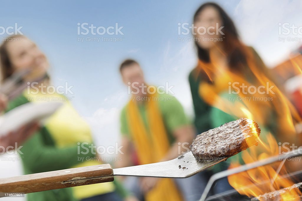 Focus on food; friends cooking out, grilling hamburgers royalty-free stock photo