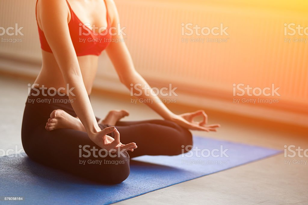 Focus on hands. Close up girl do yoga indoors. stock photo