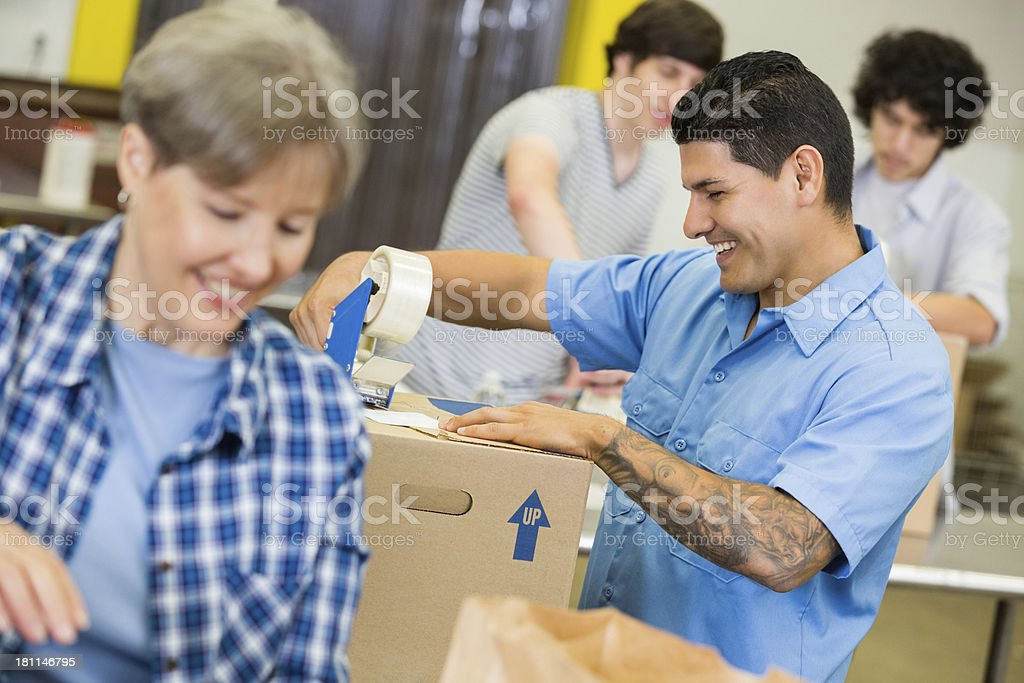 Focus on Hispanic volunteer packing boxes of food bank donations royalty-free stock photo