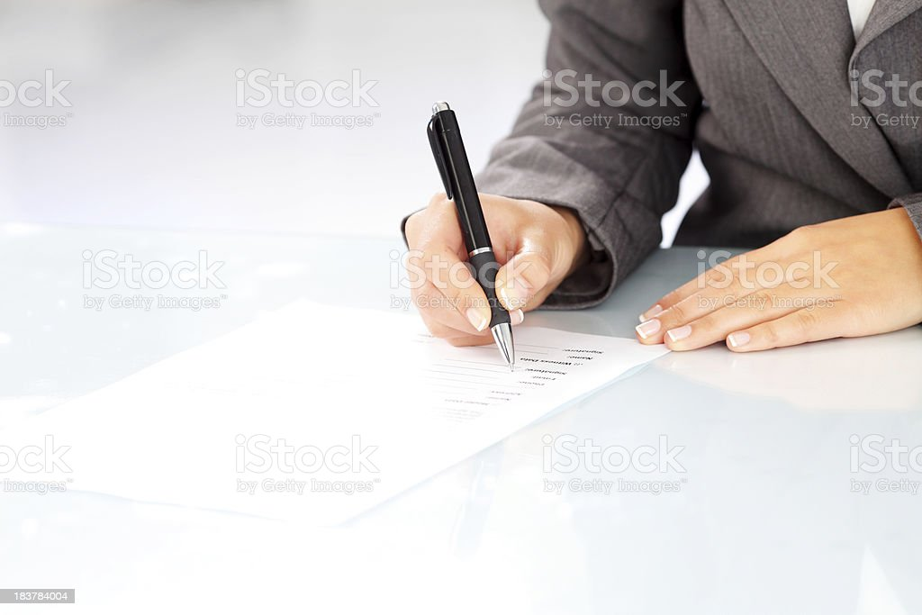 Focus on human hand - woman signing a contract. stock photo