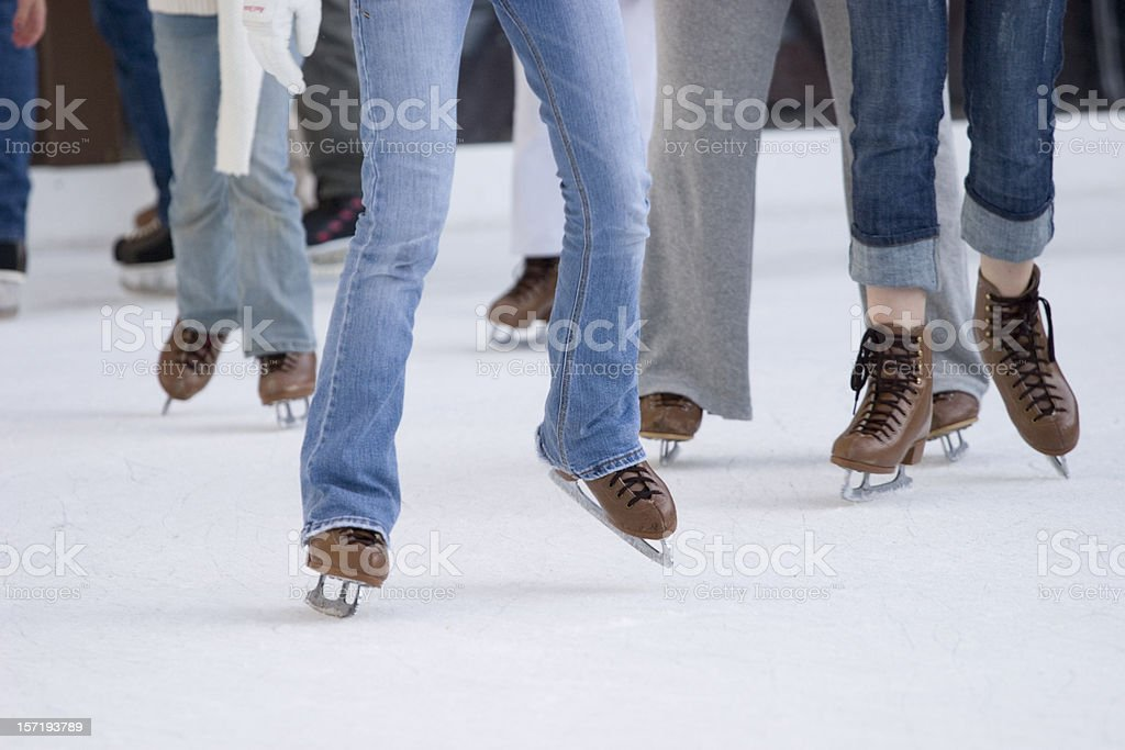 Focus on legs and skates of ice skating people royalty-free stock photo