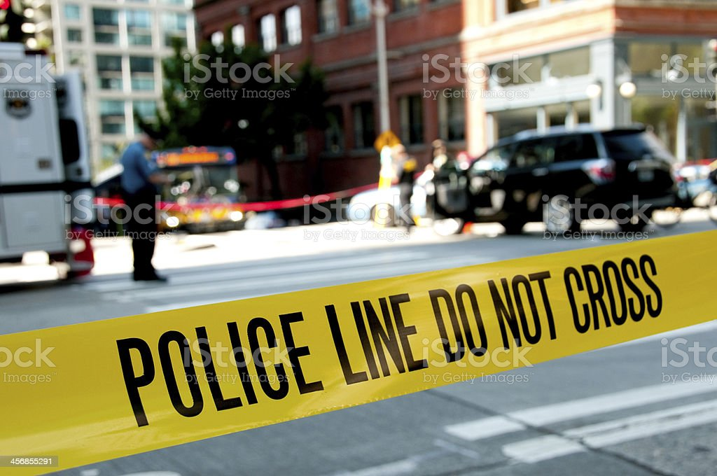 Focus on police yellow crime scene tape with scene in rear stock photo